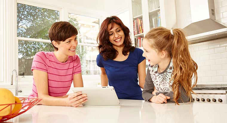 two women speak to a young girl looking at a tablet computer screen