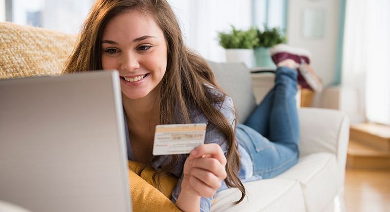 Young woman shopping online on laptop with credit card