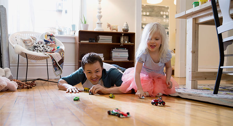 man and young girl playing with toy cars