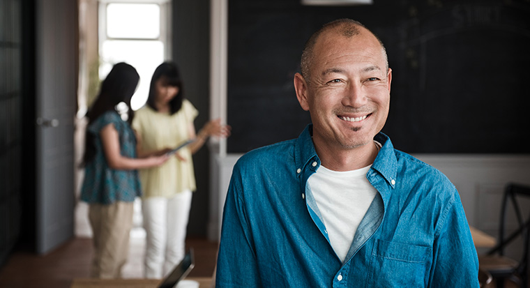 man smiling as family chats behind him