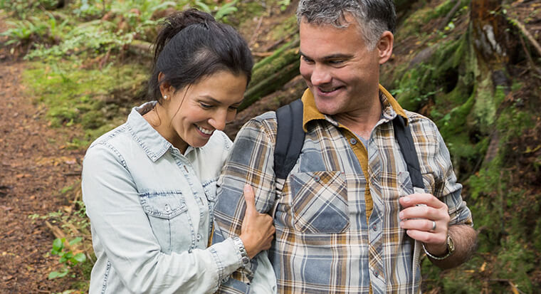 man and woman smiling while bush walking