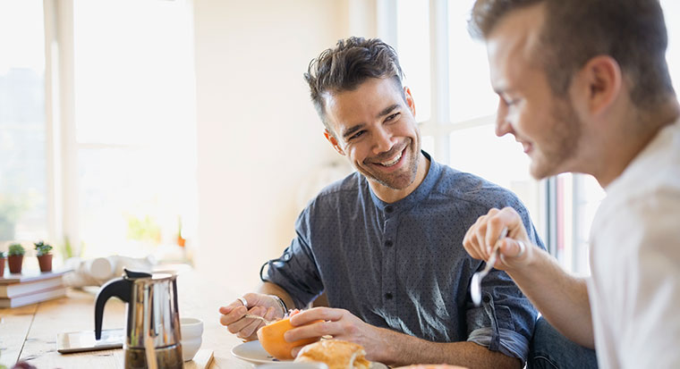 two men having breakfast together chatting