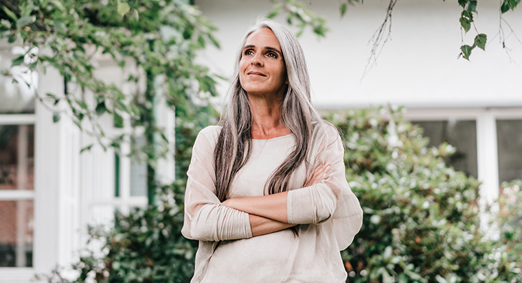 Lady with long grey hair standing outside