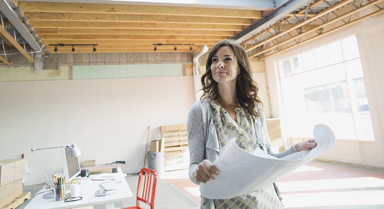 Woman reading architect plans in building project