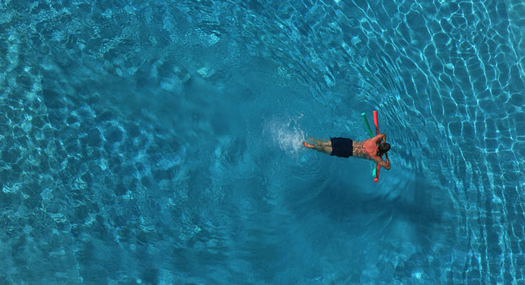 swimmer in pool buoyed by floating device