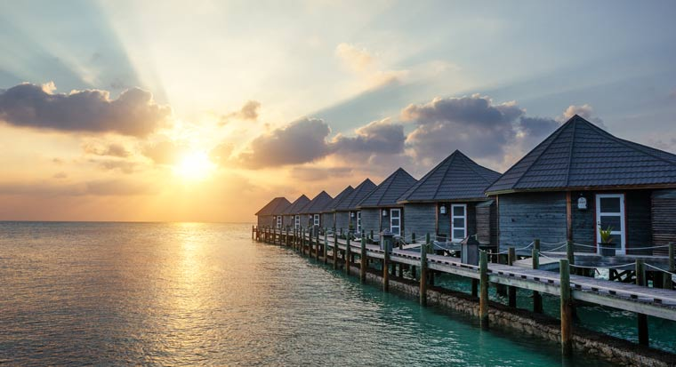 Travel island villas in front of sunset