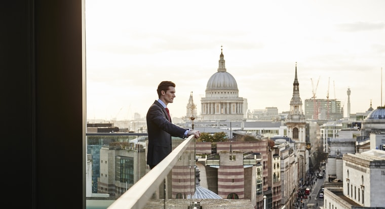 Man in a suit on a balcony overlooking St Paul's cathedral in London