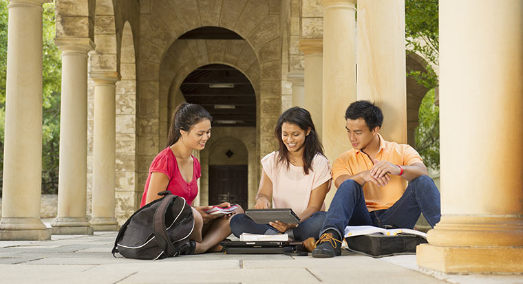 Three students sitting on the ground huddled over a tablet computer