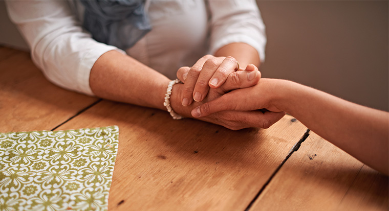 woman holding friend's hand at a table