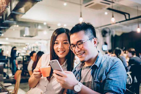 couple holding a mobile phone and coffee