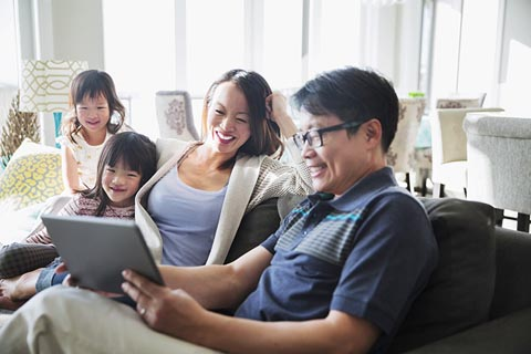 Family sitting on the sofa looking at a tablet