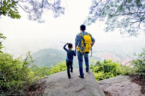 Father and son standing on a rock overlooking an Australian valley