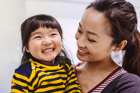 Chinese mother holding her daughter and smiling