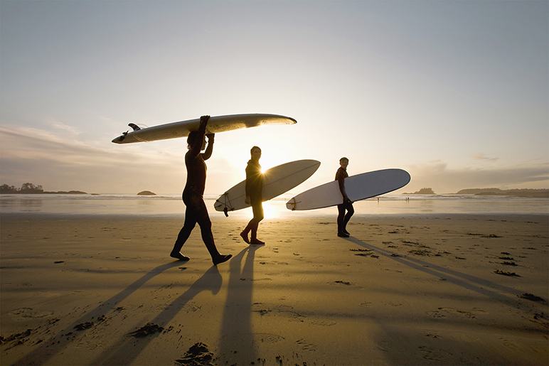 Image of three surfers walking along the beach at sunset